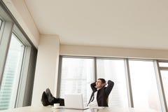 Χαλάρωση επιχειρηματιών στο γραφείο με τα πόδια επάνω στο γραφείο, copyspace στοκ φωτογραφία με δικαίωμα ελεύθερης χρήσης