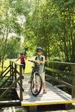 Χαλάρωση εφήβων σε ένα ταξίδι ποδηλάτων στην ξύλινη γέφυρα Στοκ Φωτογραφίες