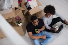 Χαλάρωση ζευγών αφροαμερικάνων στο καινούργιο σπίτι Στοκ Εικόνες