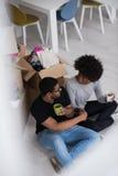 Χαλάρωση ζευγών αφροαμερικάνων στο καινούργιο σπίτι Στοκ Φωτογραφίες