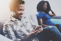 Χαλάρωση ζευγών αφροαμερικάνων χαμόγελου μαζί στον καναπέ Νέος μαύρος που χρησιμοποιεί smartphones ενώ υπόλοιπο στο σπίτι μέσα Στοκ εικόνα με δικαίωμα ελεύθερης χρήσης