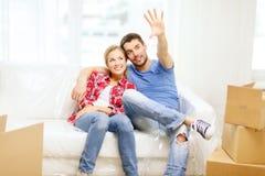 Χαλάρωση ζευγών χαμόγελου στον καναπέ στο νέο σπίτι Στοκ εικόνα με δικαίωμα ελεύθερης χρήσης
