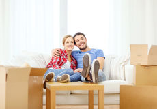 Χαλάρωση ζευγών χαμόγελου στον καναπέ στο νέο σπίτι Στοκ Φωτογραφίες