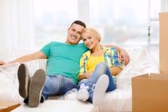 Χαλάρωση ζευγών χαμόγελου στον καναπέ στο νέο σπίτι Στοκ φωτογραφίες με δικαίωμα ελεύθερης χρήσης