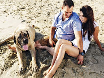 Χαλάρωση ζεύγους με το σκυλί κατοικίδιων ζώων στην παραλία. Στοκ φωτογραφίες με δικαίωμα ελεύθερης χρήσης