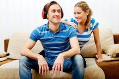 Χαλάρωση ζεύγους στον καναπέ, ακούοντας γυναίκα μουσικής ανδρών που αγκαλιάζει τον Στοκ Φωτογραφία