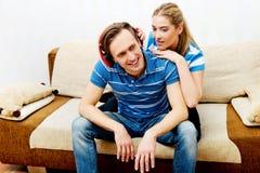 Χαλάρωση ζεύγους στον καναπέ, ακούοντας γυναίκα μουσικής ανδρών που αγκαλιάζει τον Στοκ Εικόνες