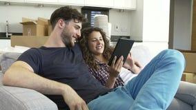Χαλάρωση ζεύγους στον καναπέ με την ψηφιακή ταμπλέτα στο νέο σπίτι απόθεμα βίντεο