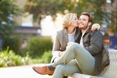 Χαλάρωση ζεύγους στον πάγκο πάρκων με το take-$l*away καφέ Στοκ φωτογραφία με δικαίωμα ελεύθερης χρήσης