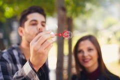 Χαλάρωση ζεύγους στο πάρκο με τον ανεμιστήρα φυσαλίδων Ο χρόνος άνοιξη… αυξήθηκε φύλλα, φυσική ανασκόπηση Στοκ Φωτογραφία