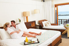 Χαλάρωση ζεύγους στο δωμάτιο ξενοδοχείου που φορά τις τηβέννους Στοκ Εικόνες