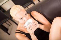 Χαλάρωση κοριτσιών σε έναν καναπέ που πίνει ένα φλιτζάνι του καφέ Στοκ Φωτογραφίες
