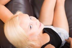 Χαλάρωση κοριτσιών σε έναν καναπέ Στοκ φωτογραφίες με δικαίωμα ελεύθερης χρήσης