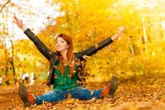 Χαλάρωση κοριτσιών στο πάρκο φθινοπώρου που ρίχνει τα φύλλα επάνω στον αέρα στοκ φωτογραφία με δικαίωμα ελεύθερης χρήσης