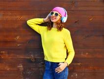 Χαλάρωση κοριτσιών χαμόγελου μόδας αρκετά δροσερή που ακούει τη μουσική στα ακουστικά που φορούν το ζωηρόχρωμο ρόδινο κίτρινο πλε Στοκ Φωτογραφίες