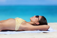 Χαλάρωση μαυρίσματος γυναικών γυαλιών ηλίου παραλιών στο μπικίνι στοκ εικόνες