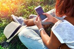 Χαλάρωση με έναν κινητό Χρόνος σπασιμάτων Νέα γυναίκα χρησιμοποιώντας το κινητό τηλέφωνο και καθμένος στη χλόη Στοκ Φωτογραφία