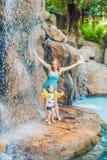 Χαλάρωση μητέρων και γιων κάτω από έναν καταρράκτη στο aquapark Στοκ Εικόνες