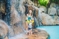 Χαλάρωση μητέρων και γιων κάτω από έναν καταρράκτη στο aquapark Στοκ φωτογραφίες με δικαίωμα ελεύθερης χρήσης