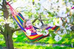 Χαλάρωση μικρών κοριτσιών σε μια αιώρα Στοκ Εικόνες