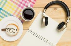 Χαλάρωση μουσικής και γραψίματος στον καφέ με το σημειωματάριο Στοκ Εικόνες