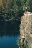 Χαλάρωση νέων κοριτσιών στον απότομο βράχο του κοντινού νερού νησιών Στοκ Φωτογραφία