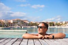 Χαλάρωση νεαρών άνδρων στην πισίνα στοκ εικόνες με δικαίωμα ελεύθερης χρήσης