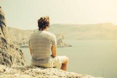 Χαλάρωση νεαρών άνδρων στη δύσκολα θάλασσα και τα βουνά απότομων βράχων στο υπόβαθρο Στοκ φωτογραφίες με δικαίωμα ελεύθερης χρήσης