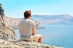Χαλάρωση νεαρών άνδρων στη δύσκολη συνεδρίαση απότομων βράχων και κοίταγμα στη θάλασσα Στοκ Εικόνα