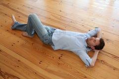 Χαλάρωση νεαρών άνδρων στο ξύλινο πάτωμα στοκ εικόνα με δικαίωμα ελεύθερης χρήσης