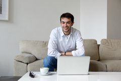 Χαλάρωση νεαρών άνδρων στο σπίτι με το lap-top Στοκ εικόνες με δικαίωμα ελεύθερης χρήσης