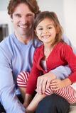Χαλάρωση πατέρων και κορών στον καναπέ από κοινού στοκ φωτογραφία
