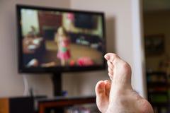 Χαλάρωση προσέχοντας κάποια TV Στοκ Φωτογραφία