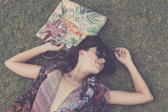 χαλάρωση χλόης Η τοπ άποψη της όμορφης νέας γυναίκας στα γυαλιά ηλίου και το pareo που βρίσκεται στην πράσινη χλόη με την παραλία Στοκ Εικόνες