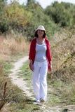 Χαλαρωμένη γηράσκουσα γυναίκα που περπατά σε μια πορεία που απολαμβάνει το καλοκαίρι Στοκ φωτογραφία με δικαίωμα ελεύθερης χρήσης