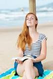 Χαλαρωμένη γυναίκα με το βιβλίο στην παραλία Στοκ Εικόνα