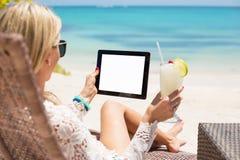 Χαλαρωμένη γυναίκα που χρησιμοποιεί τον υπολογιστή ταμπλετών στην παραλία