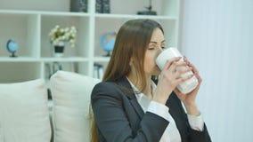 Χαλαρωμένη επιχειρηματίας που απολαμβάνει τη συνεδρίαση καφέ της σε έναν καναπέ στο γραφείο της απόθεμα βίντεο