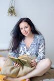 Χαλαρωμένη ευτυχής γυναίκα που διαβάζει μια συνεδρίαση βιβλίων σε έναν καναπέ στο σπίτι Στοκ φωτογραφία με δικαίωμα ελεύθερης χρήσης