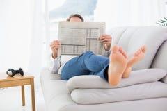 Χαλαρωμένη εφημερίδα ανάγνωσης ατόμων στον καναπέ στοκ φωτογραφία