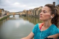Χαλαρωμένη μουσική ακούσματος γυναικών ικανότητας μπροστά από το vecchio ponte Στοκ φωτογραφίες με δικαίωμα ελεύθερης χρήσης