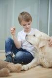 Χαλαρωμένη συνεδρίαση αγοριών με το σκυλί του στο πάτωμα στοκ φωτογραφίες