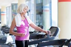 Χαλαρωμένη χαμογελώντας γκρίζα μαλλιαρή γυναίκα που στέκεται treadmill Στοκ Εικόνα
