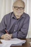 Χαλαρωμένος ανώτερος επιχειρηματίας ή δάσκαλος που εργάζεται στο γραφείο του Στοκ εικόνες με δικαίωμα ελεύθερης χρήσης