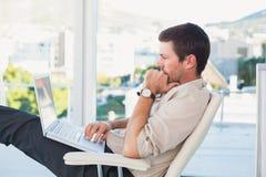 Χαλαρωμένος επιχειρηματίας με ένα lap-top Στοκ φωτογραφία με δικαίωμα ελεύθερης χρήσης