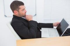 Χαλαρωμένος επιχειρηματίας με ένα lap-top Στοκ Εικόνες