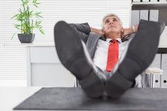 Χαλαρωμένος επιχειρηματίας με τα πόδια του επάνω Στοκ φωτογραφία με δικαίωμα ελεύθερης χρήσης