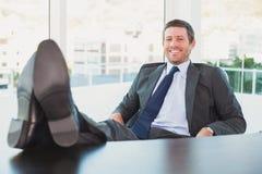 Χαλαρωμένος επιχειρηματίας με τα πόδια του επάνω Στοκ Εικόνες