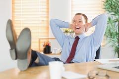 Χαλαρωμένος επιχειρηματίας με τα πόδια του επάνω Στοκ Φωτογραφίες