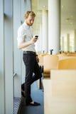 Χαλαρωμένος επιχειρηματίας που έχει ένα κενό και που χρησιμοποιεί το τηλέφωνό του Στοκ Φωτογραφία